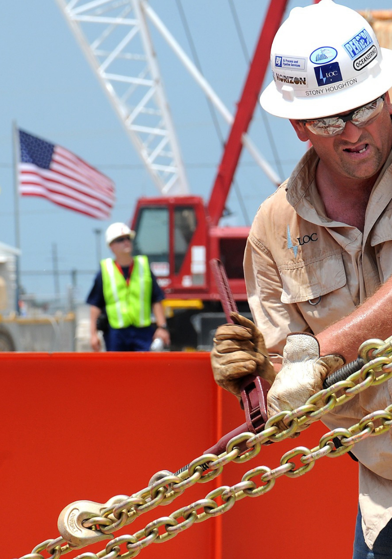 A worker in a hardhat working with a large chain